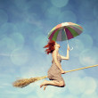 Young red-haired witch on broom flying in the sky with umbrella — Stock Photo #17006747
