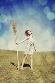 Young red-haired witch at green grass field with broom. — Stock Photo