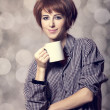 Style girl in shirt with cup at studio. — Stock Photo