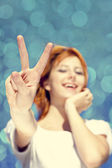 Portrait of red-haired girl in white which show hand V symbol. — Stock Photo
