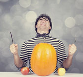 The young mad men try to eat two apples and pumpkin. — Stock Photo