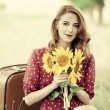 Stock Photo: Redhead girl with sunflower at outdoor.