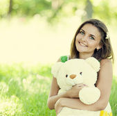 Beautiful teen girl with Teddy bear in the park at green grass. — Stock Photo