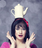Brunette women with teapot on head. — Stock Photo