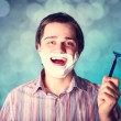 Man shaving isolated on blue background - Stock Photo