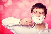 человек для бритья, изолированные на красном фоне — Стоковое фото