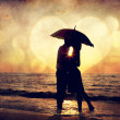 Couple kissing under umbrella at the beach in sunset. Photo in o — Стоковая фотография