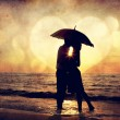 Couple kissing under umbrella at the beach in sunset. Photo in o - 图库照片