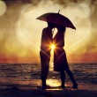 Stock Photo: Couple kissing under umbrella at the beach in sunset. Photo in o