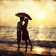 Royalty-Free Stock Photo: Couple kissing under umbrella at the beach in sunset. Photo in o