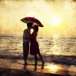 Couple kissing under umbrella at the beach in sunset. Photo in o — Stock Photo #18858731