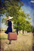 Redhead girl with suitcase at tree — Stock Photo