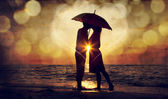 Coppia baciarsi sotto l'ombrellone in spiaggia nel tramonto. foto in o — Foto Stock