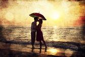 Pár líbání pod slunečník na pláži v západu slunce. foto v o — Stock fotografie