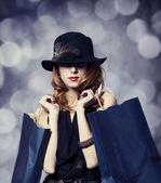 Stijl roodharige meisje met shopping tassen. — Stockfoto