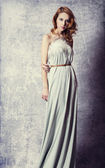 Beautiful woman posing in a long dress — Stock Photo