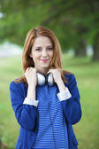 Young fashion girl with headphones at spring outdoor. — Stock Photo