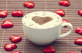 Cup of coffee with heart symbol and candy around. — Stock Photo