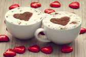 Two cup of coffee with heart symbol and candy around. — Stok fotoğraf