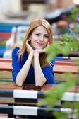Styl rudowłosy dziewczyna siedzi na ławce w kawiarni — Zdjęcie stockowe