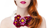 Beautiful redhead girl with flowers — Stock Photo