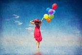 Brunett tjej med färg ballonger på kusten. — Stockfoto