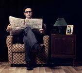 Człowiek z gazety, siedząc w fotelu vintage — Zdjęcie stockowe