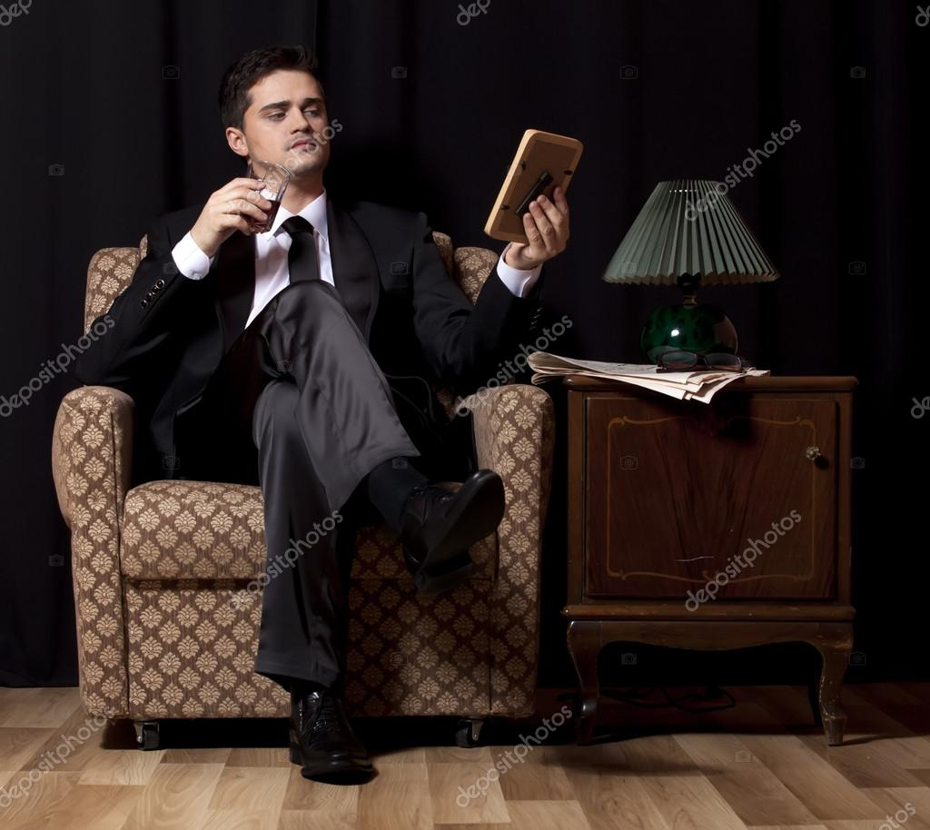 Man with alcohol sitting in vintage armchair stock photo for Sitting in armchair