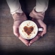 Woman holding hot cup of coffee, with heart shape — Stock Photo #21178405