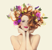 Beautiful redhead girl with flowers isolated. — Stock Photo