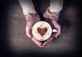 Woman holding hot cup of coffee, with heart shape — Stockfoto