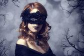 Beautiful women in carnival mask. Photo with forest at backgroun — Stock Photo