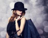 Stil rothaarige mädchen mit einkaufstaschen. — Stockfoto