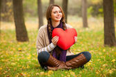 Girl with toy heart at autumn park. — Stock Photo