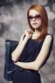 Chica pelirroja estilo con bolsas de compras. — Foto de Stock