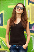 Style teen girl in sunglasses near graffiti background. — Stock Photo
