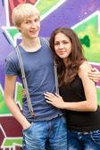 Style teen couple near graffiti background. — Stock Photo