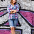 Style teen girl standing near graffiti wall. — Stock Photo #22349229