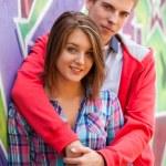 Young couple near graffiti background. — Stock Photo