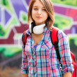 Style teen girl with backpack standing near graffiti wall. — Stock Photo
