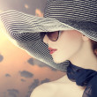 Stock Photo: Fashion women in wide hat at sunrise