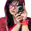 Teen girl in red with camera at white background. — Stock Photo