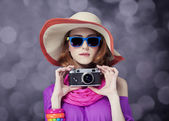 Funny redhead girl in hat with camera and bokeh at background — Stock Photo