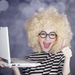 Portrait of funny girl in blonde wig with laptop. Studio shot. — Stock Photo