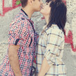 Young couple kissing near graffiti background. - Stock fotografie