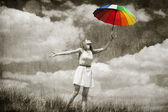 Beautifu girl with umbrella and suitcase at sky background. — Stock Photo