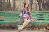 Style redhead girl sitting on the bench — Stock Photo