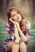 Chica pelirroja estilo sentado en el banquillo — Foto de Stock