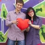Teens with heart near graffiti wall. — Stock Photo