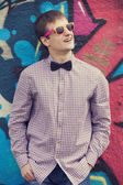 Style teen in glasses standing near graffiti wall. — Stock Photo